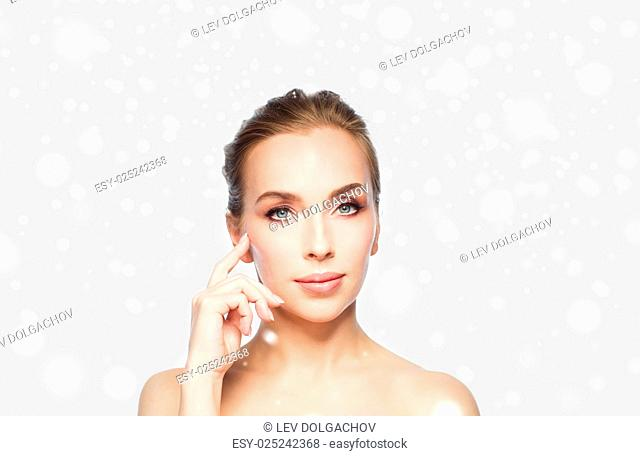 beauty, people, winter and plastic surgery concept - beautiful young woman showing her cheekbone over gray background and snow