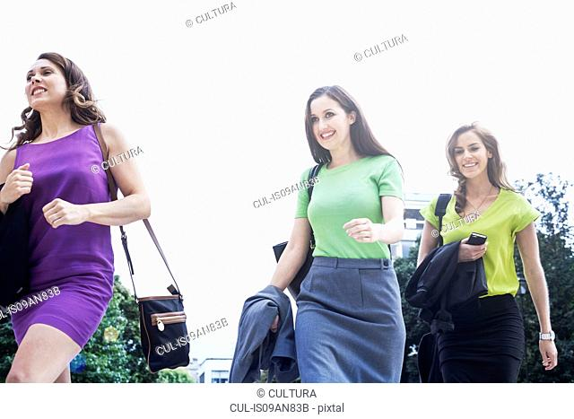 Three businesswomen walking together, outdoors, low angle view