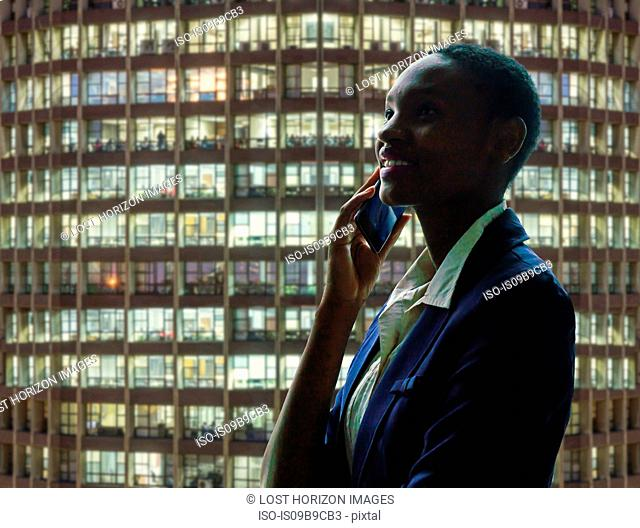 Businesswoman using phone, facade of neighbouring building in background