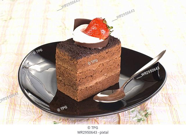 Piece of Chocolate cake with strawberry in black plate on the table