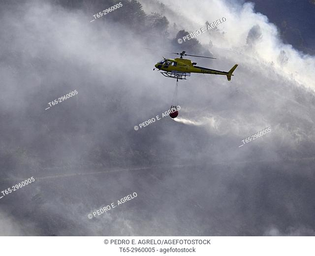 Forest fires in Galicia, in the mountain of the Ancares lucenses, a helicopter performs cooling tasks. Galicia, Spain
