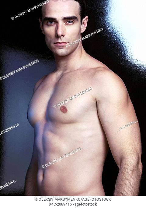 Portrait of a sexy handsome man with muscular bare torso on black background