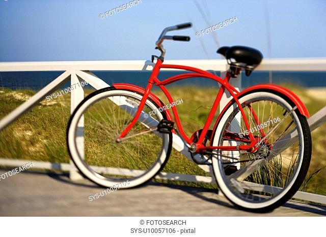 Red beach cruiser bicycle leaning against walkway rail on beach on Bald Head Island, North Carolina