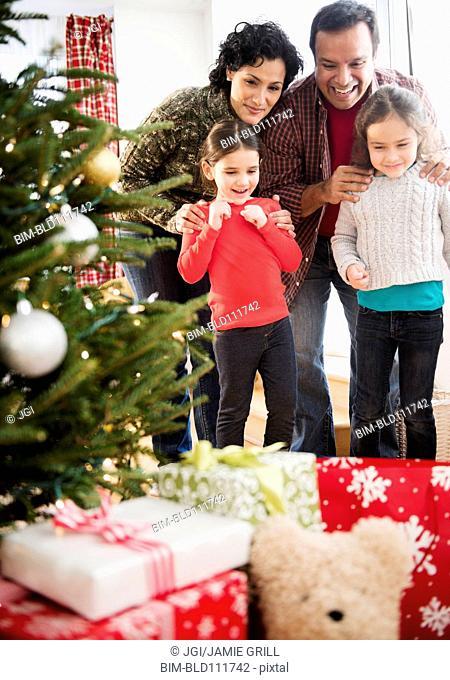 Family examining presents under Christmas tree