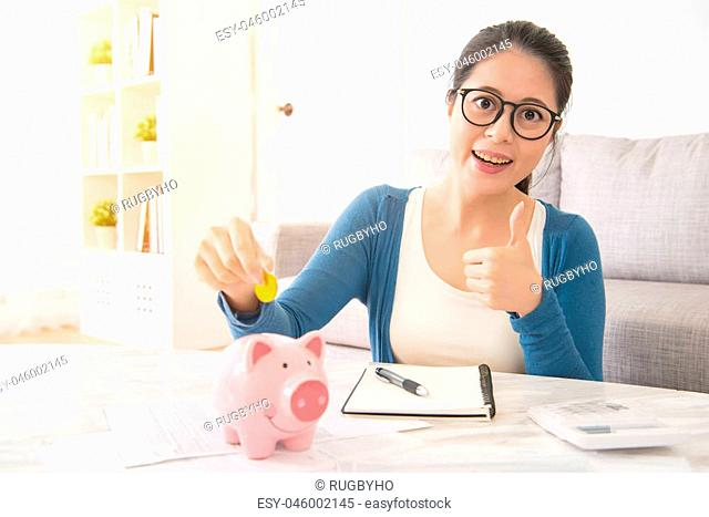 happy asian girl student with holding money savings into piggy bank for the college scholarship showing thumb up sitting on sofa in the living room at home