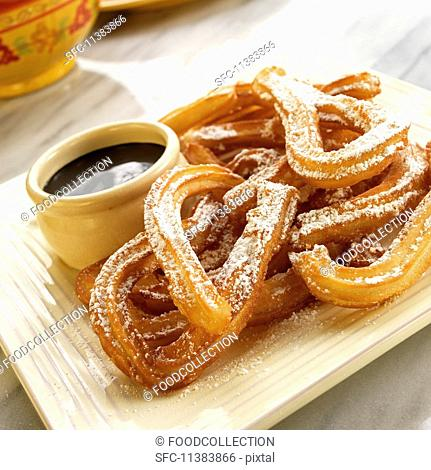 Churros with icing sugar and dark chocolate sauce (Mexico)