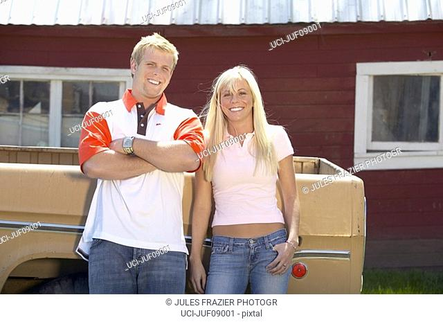 Couple leaning against pick-up truck