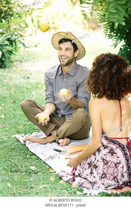 Happy couple having a picnic in a park with man juggling with apples
