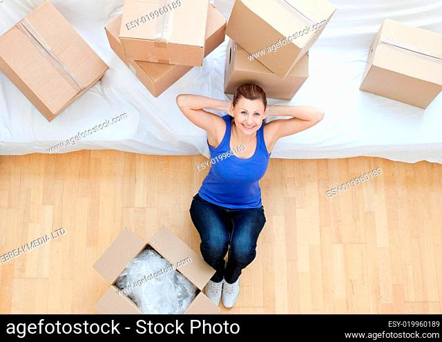 Beautiful woman sitting between boxes at home