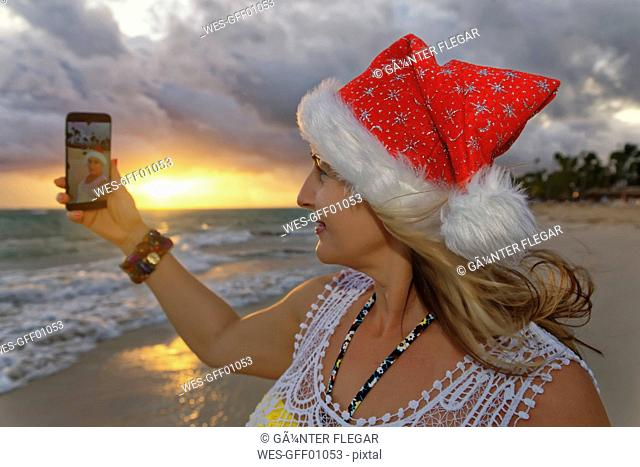 Carribean, Dominican Republic, Punta Cana, woman with Christmas cap taking selfie on the beach