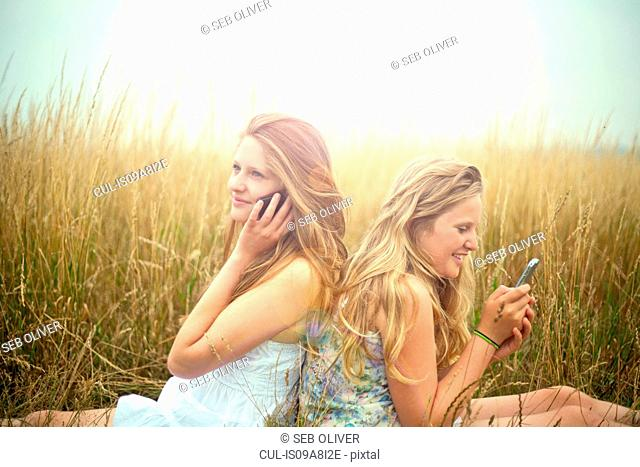 Girls using smartphones in a field, back to back