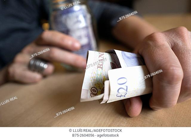 Woman hands with sterling notes in a glass jar and a hand