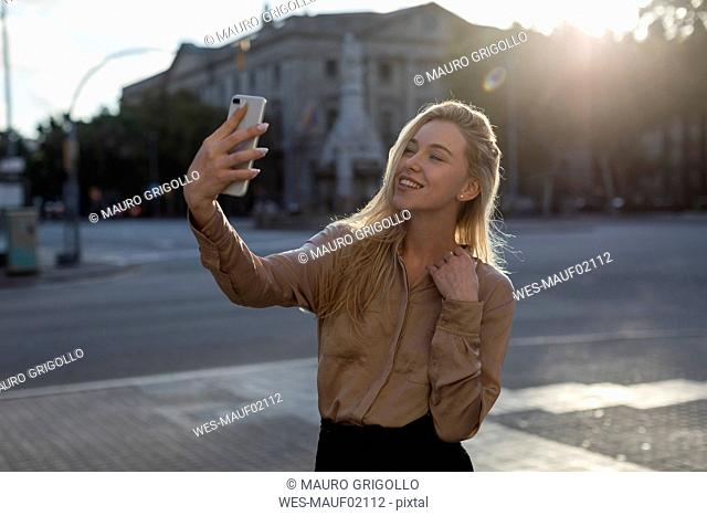 Happy young woman taking a selfie in the city