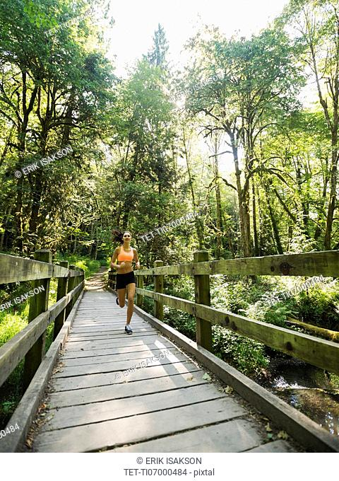 Young woman jogging on footbridge