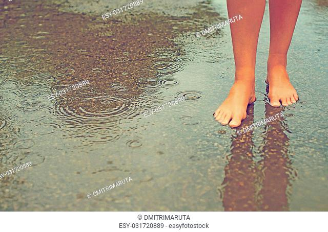 Woman enjoying tropical rain. Legs