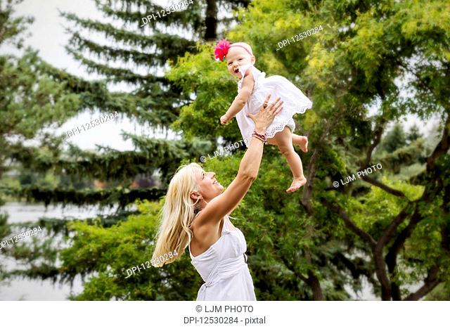 A beautiful young mother with long blonde hair enjoying quality time with her cute baby daughter and tossing her in the air in a city park on a summer day;...