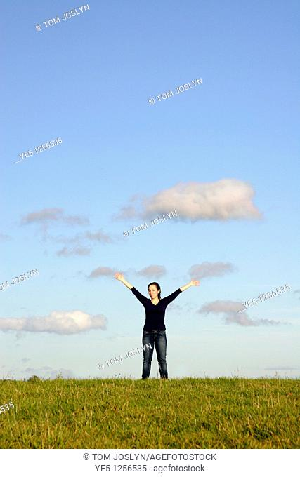 Woman standing on grass hill with arms in the air, England, UK