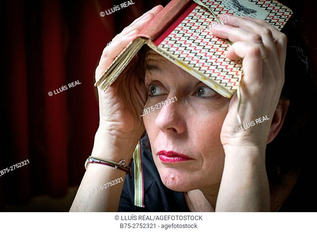 Middle-aged woman with a book over her head looking away