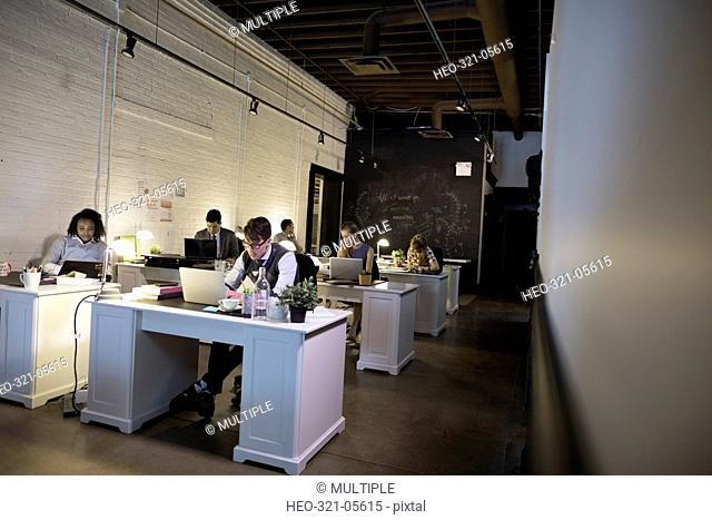 Creative business people working at desks in open plan office