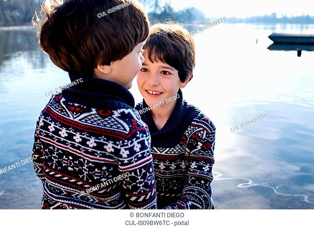 Boy and toddler brother in matching sweaters on lakeside, Lake Como, Lecco, Lombardy, Italy