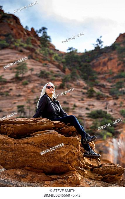 Caucasian woman sitting on edge of rock