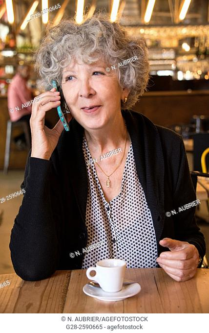 Beautiful senior woman, with grey hair, happy looking, using her i-phone and smiling, with a cup of coffee in front of her, in a cafe