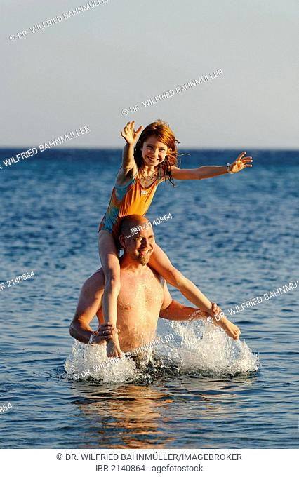 Father and daughter splashing around in the sea