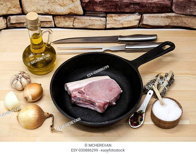 A piece of delicious fresh raw pork close-up on a cast-iron frying pan, onions, garlic, spices, salt, olive oil, fork, knife on a rustic kitchen table