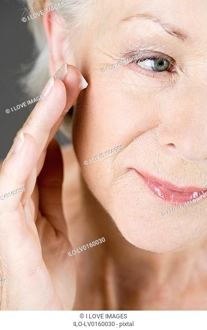 A senior woman applying moisturiser to her face