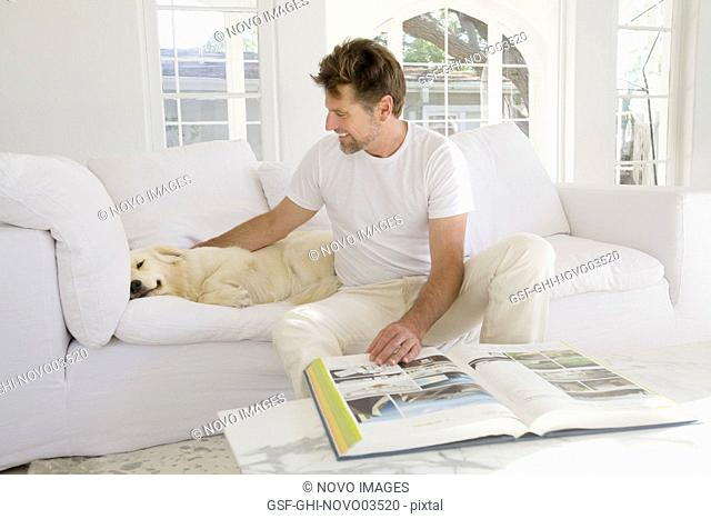 Mid-Adult Man Reading Large Book in Living Room while Petting Pet Dog III