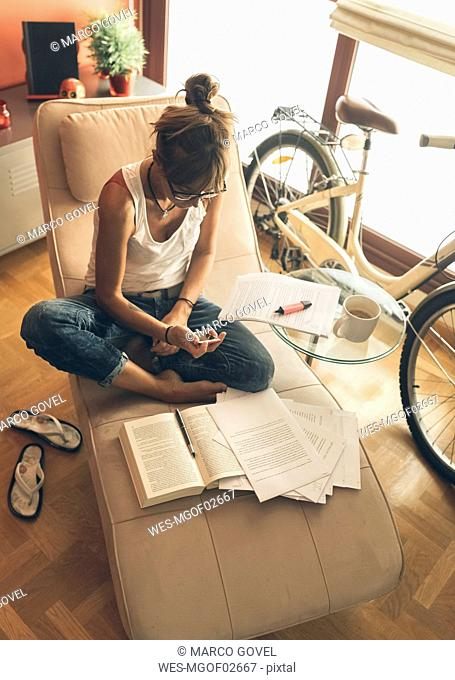 Woman at home with cell phone working on script