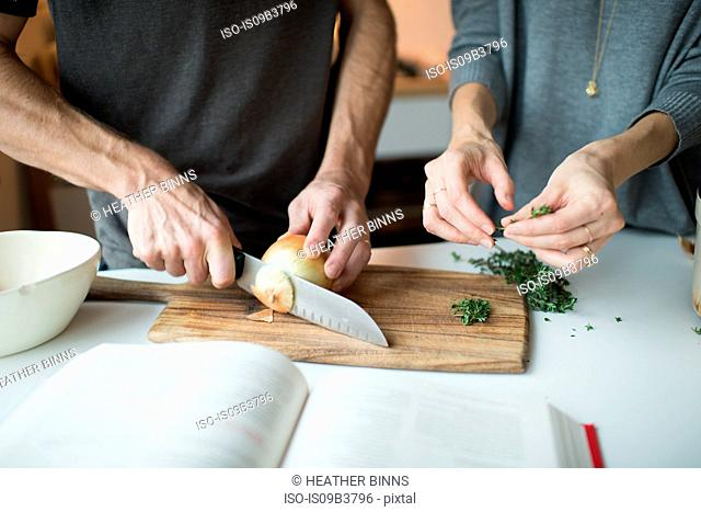 Mid section of couple chopping onions in kitchen