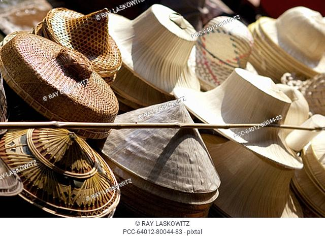 Thailand, Bangkok, Damnoen Saduak Floating Market in Ratchaburi Province, traditional straw hats for sale