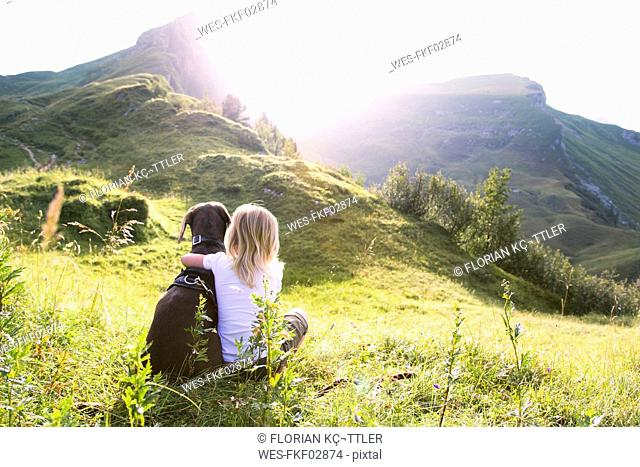 Austria, South Tyrol, young girl sitting with dog on meadow