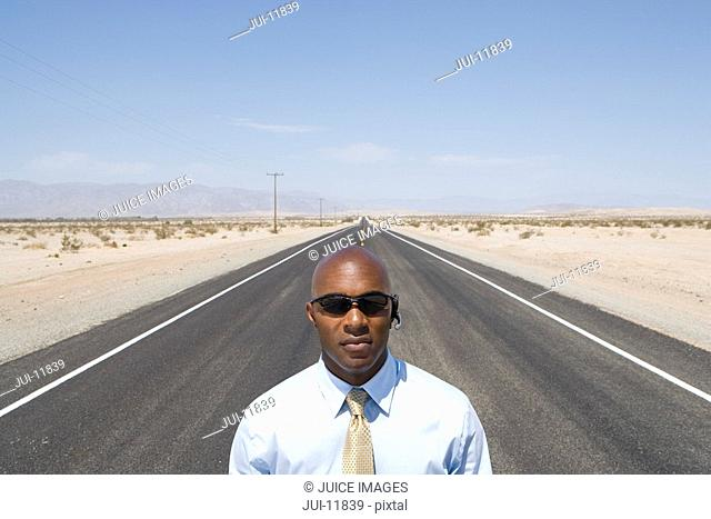 Businessman in sunglasses in middle of road in desert, elevated view
