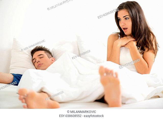 Young attractive girl after waking up in bed, looking with surprise erection her boyfriend who still sleeps covered with a sheet