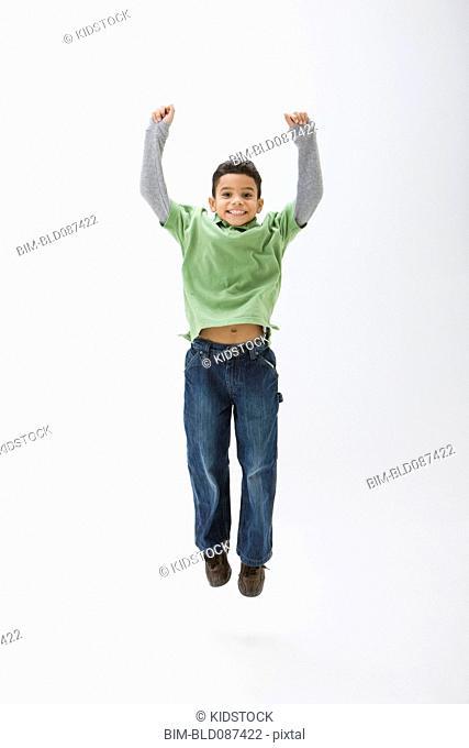 Hispanic boy cheering and jumping
