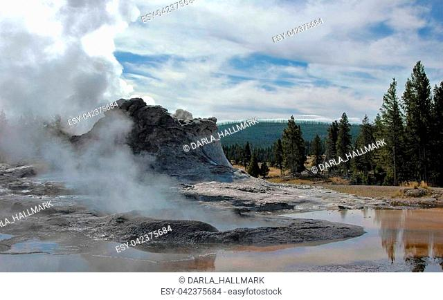 Yellowstone National Park, Castle geyser beginning to erupt, and reflecting in it's own expelled waters