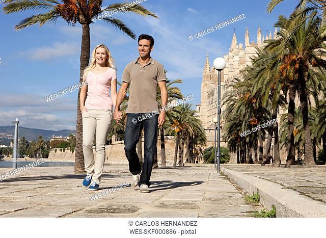 Spain, Mallorca, Palma, Couple walking along allee, smiling