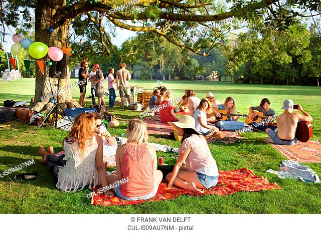 Group of friends listening to music under park tree at sunset party