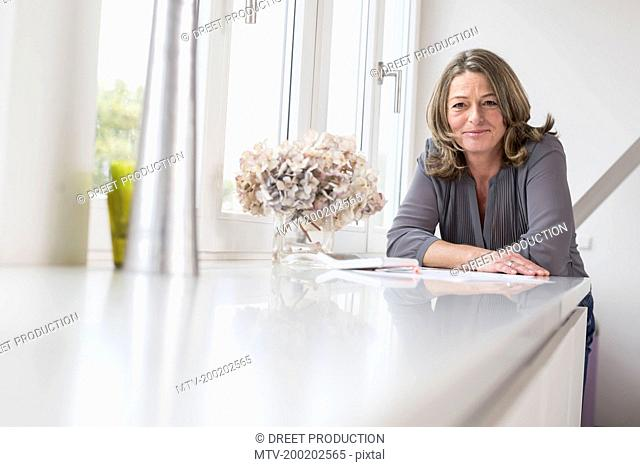 Smiling mature woman leaning on table, portrait