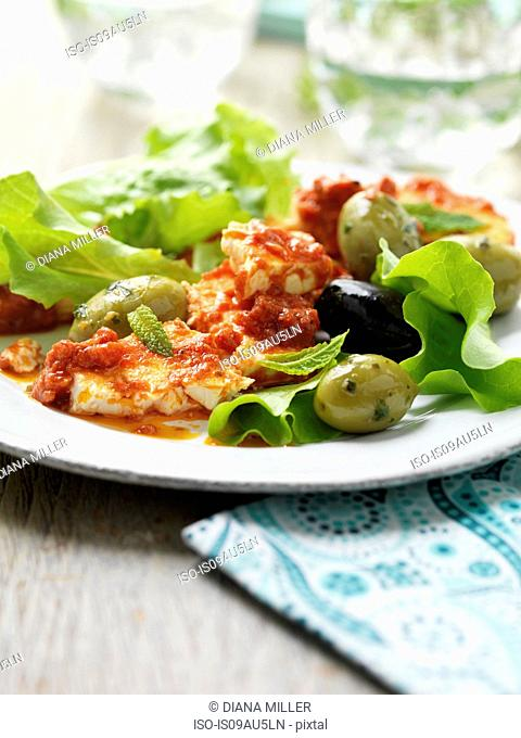Plate of feta bake with black and green olives and lettuce on garden table
