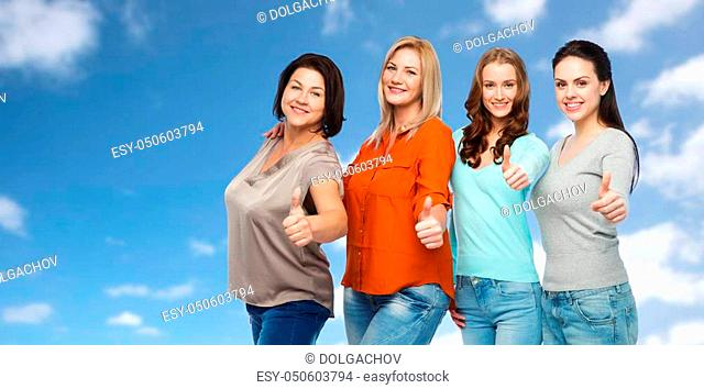 friendship, fashion, body positive, gesture and people concept - group of happy different size women in casual clothes showing thumbs up over blue sky and...
