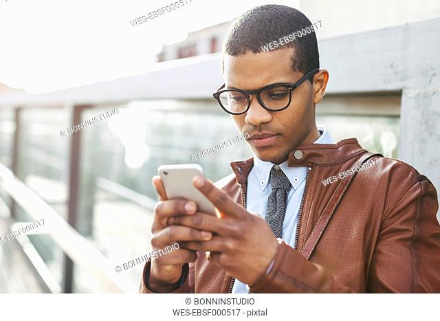 Portrait of businessman with smartphone wearing leather jacket and glasses