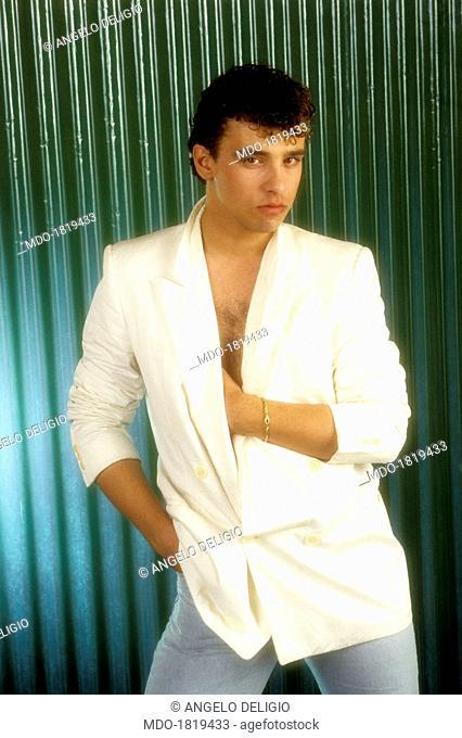Italian singer-songwriter Eros Ramazzotti posing wearing white jacket. Italy, 1984
