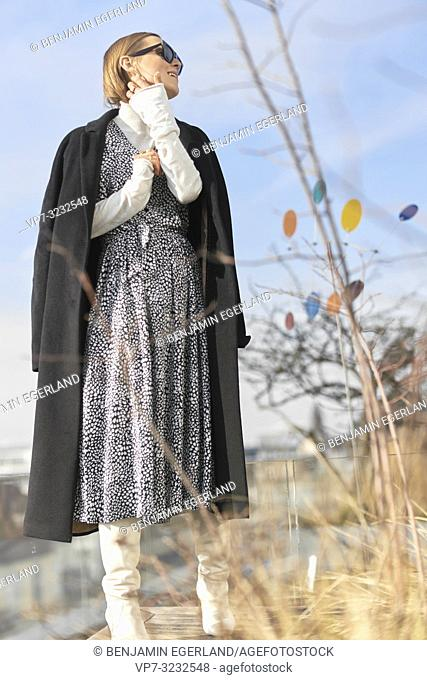 well-dressed fashionable blogger woman wearing dress and coat, in Munich, Bavaria, Germany
