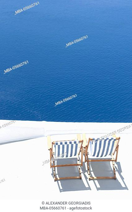 Deckchairs on rooftop with view to the Caldera, Oia, Santorini, Greece