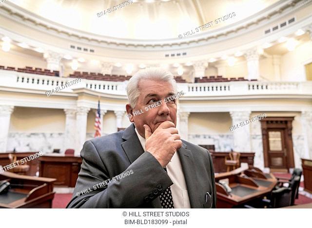 Caucasian politician thinking in capitol building