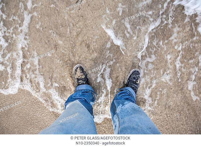 Man's feet in the water at a beach