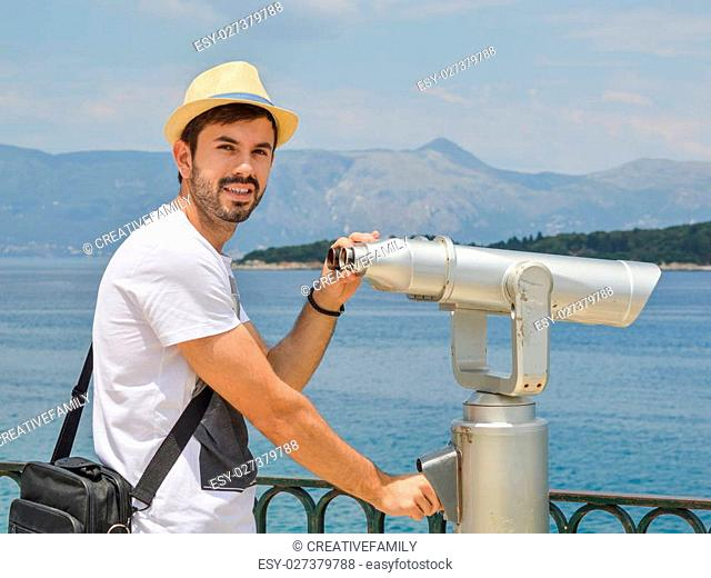 Young bearded man holding public binoculars at the seaside wearing straw on a sunny day